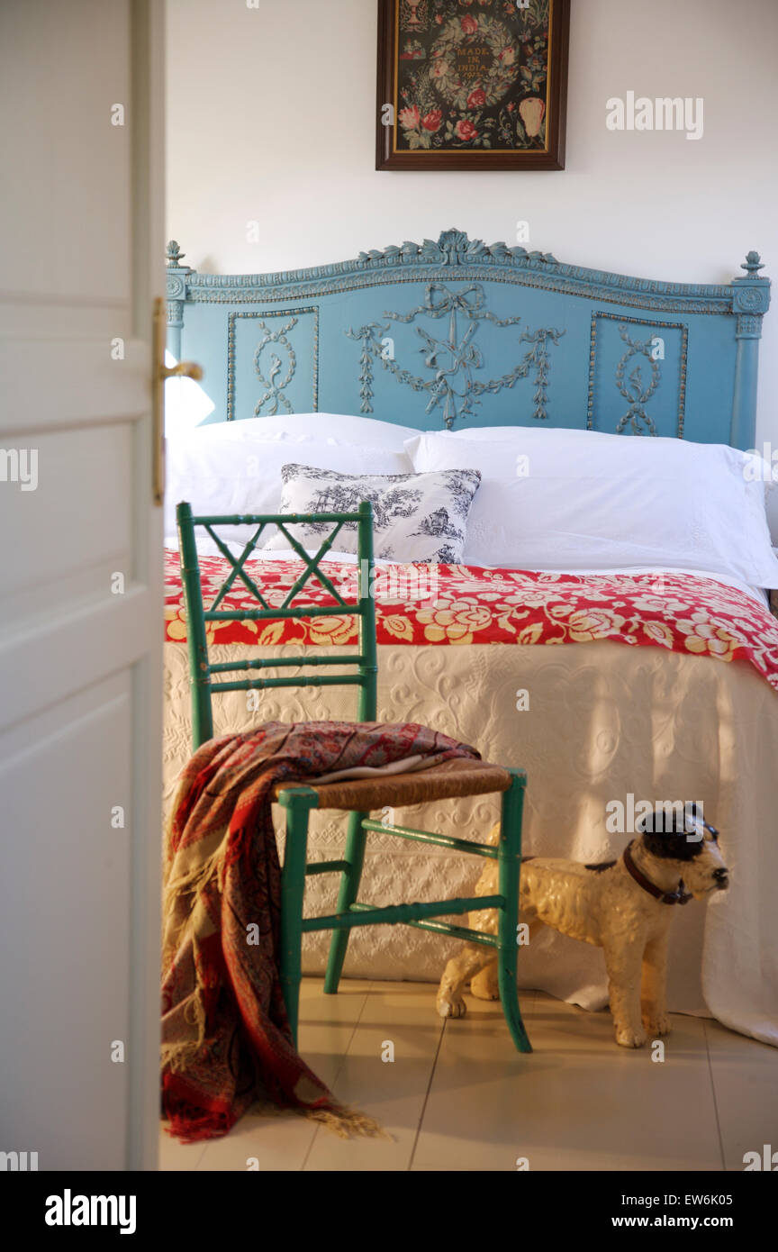 Toy dog beside painted chair in French country bedroom with white ...