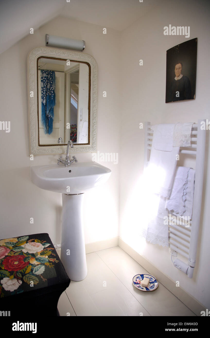 Mirror above pedestal basin in white cottage bathroom with a wall ...