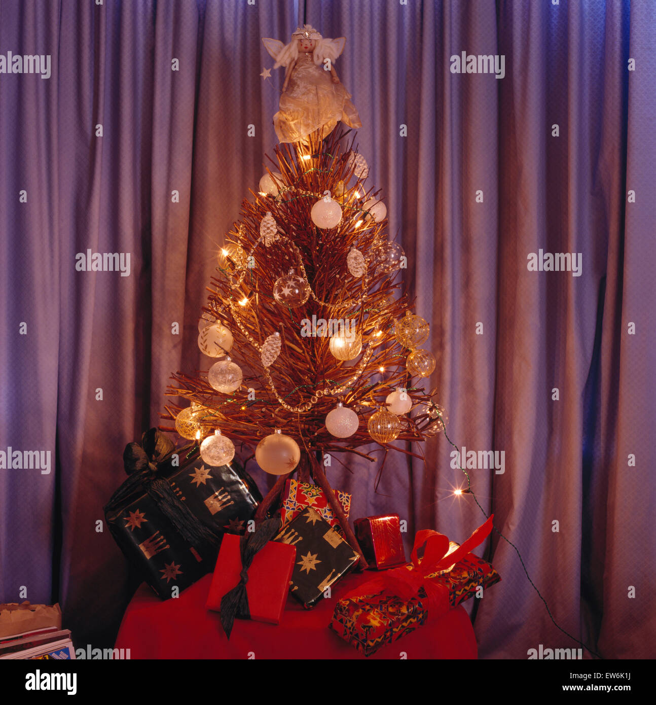 twig christmas tree with glass baubles and lights on a table with wrapped presents