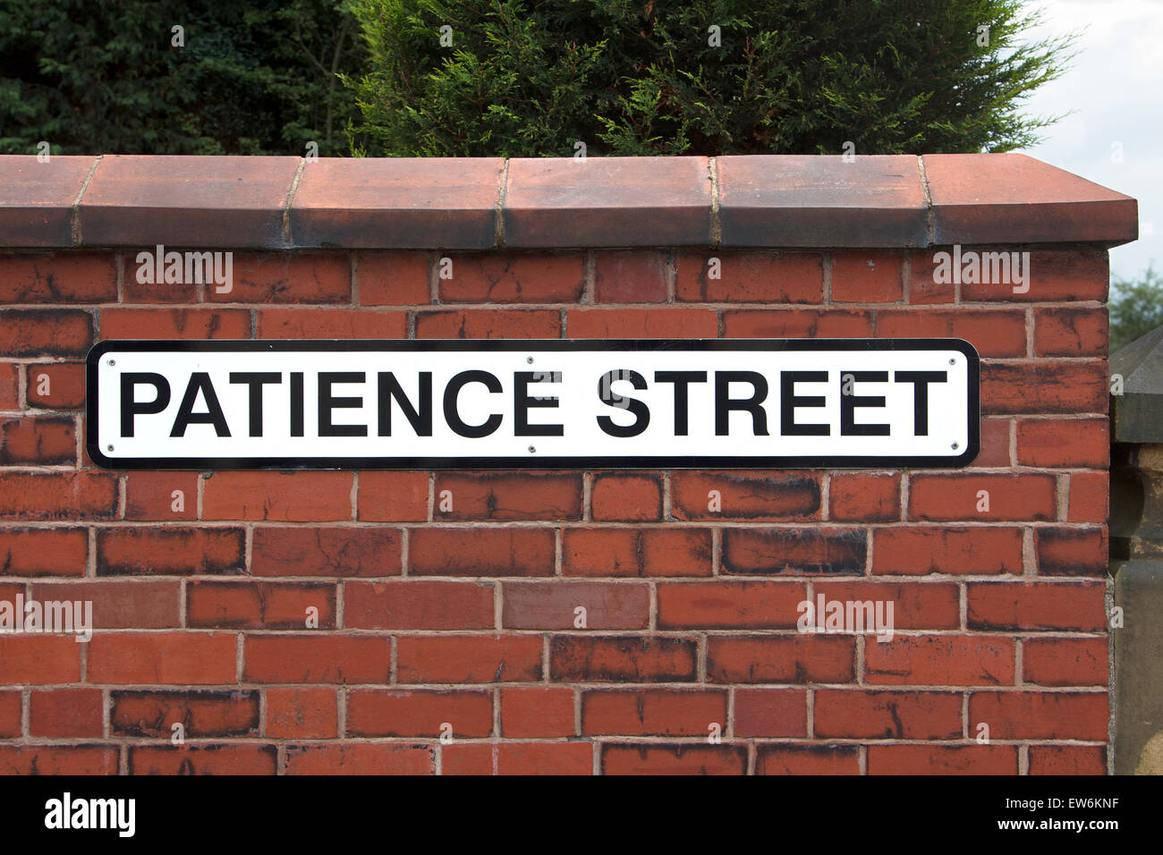 'Patience' street sign on red brick wall - Stock Image