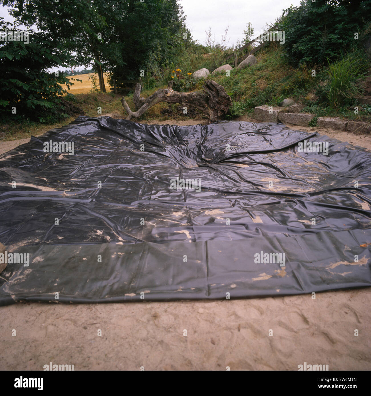 Black plastic sheeting on area to be made into a pond - Stock Image