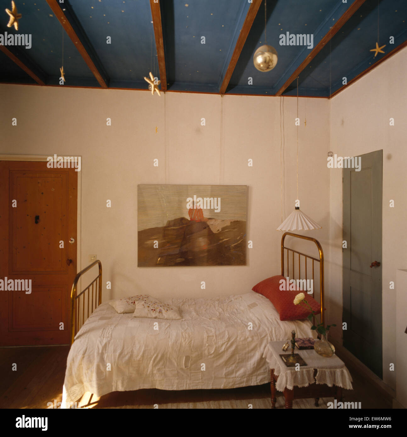 Picture on wall above brass bed in eighties Swedish bedroom - Stock Image