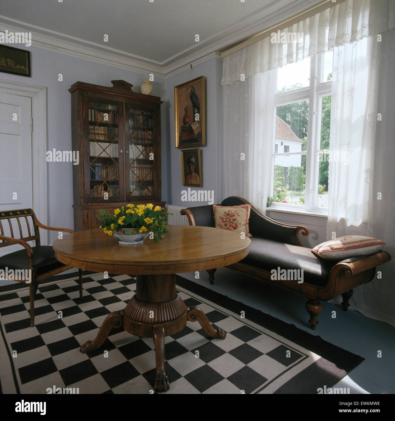 Antique chaise longue and table in Swedish dining room with black+white chequerboard rug on the floor - Stock Image