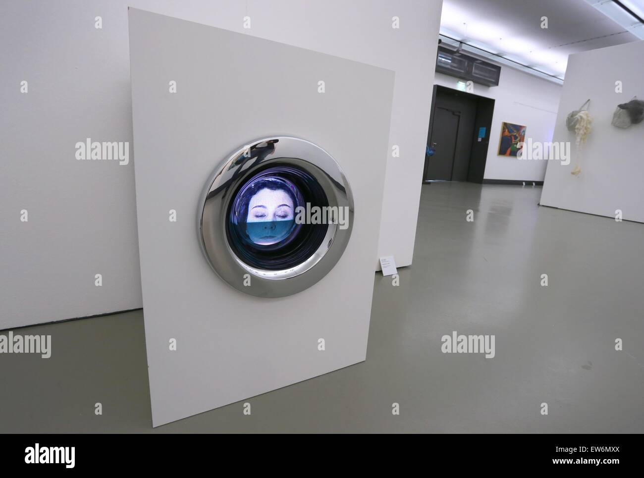 Wuerzburg, Germany. 18th June, 2015. An actress in a video is seen through the hatch of a stylised washing machine - Stock Image