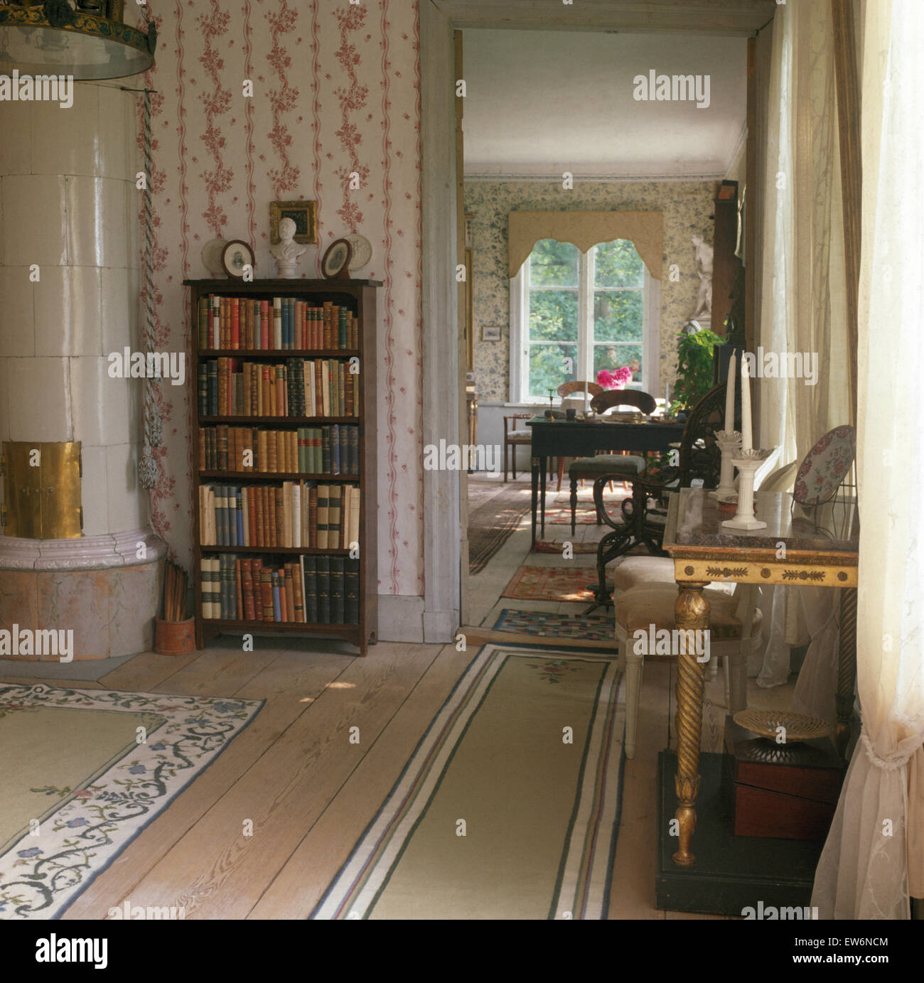 Bookcase beside white ceramic stove in elegant Swedish drawing room with rugs on stripped wooden floor - Stock Image