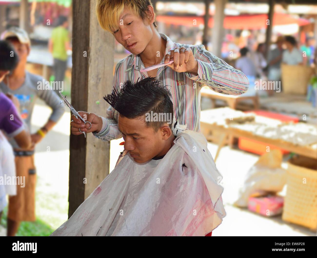 Man having haircut at a river side stall at one of the 5 day rotating markets at  Nampan Market on Inle Lake,Shan - Stock Image