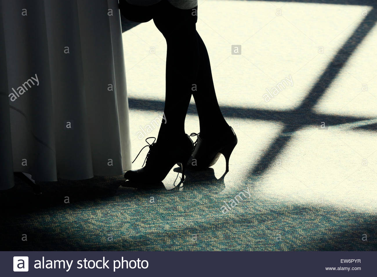 A woman in high heels stands in shafts of light on the floor. - Stock Image