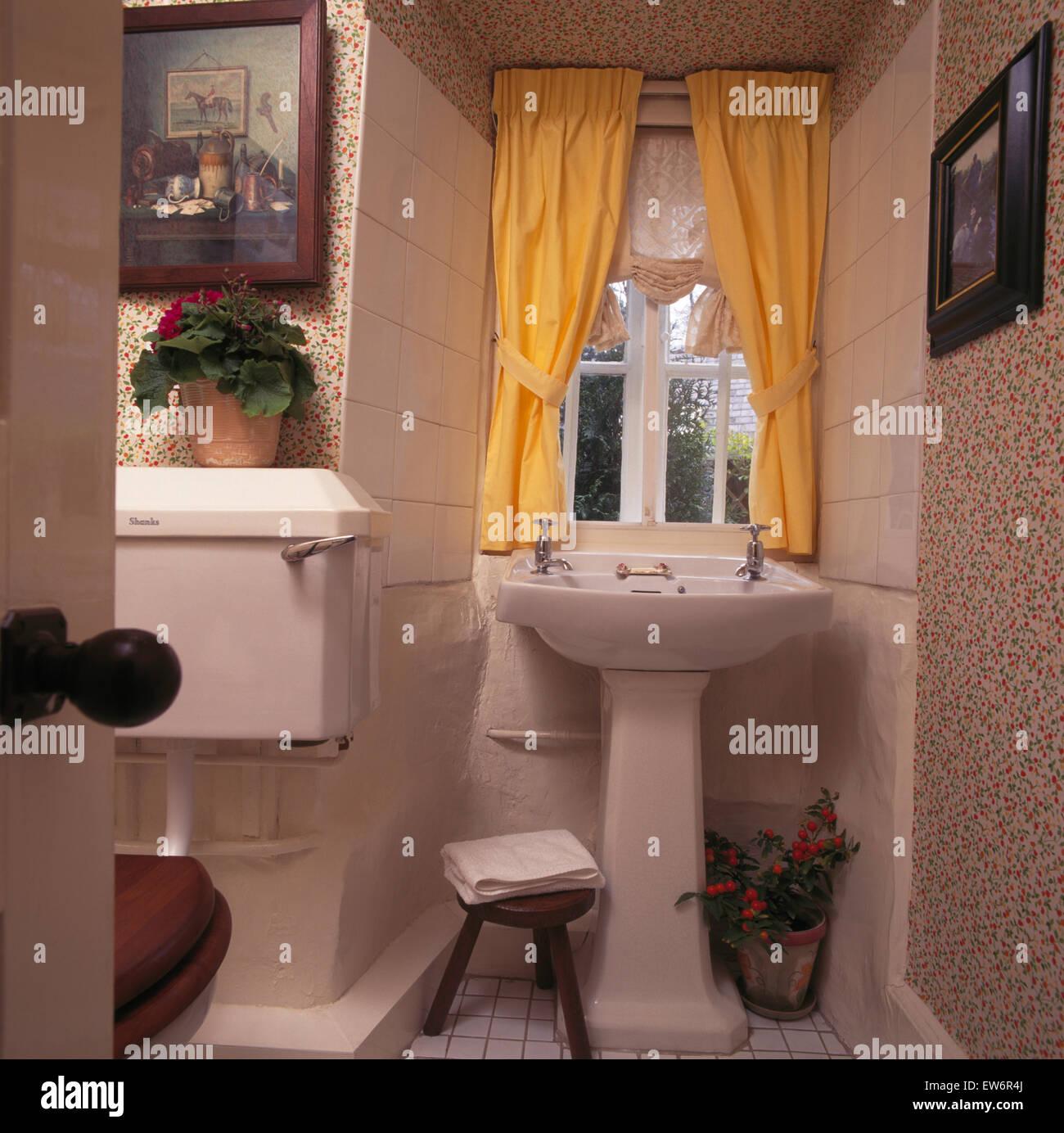 Yellow Curtains On Window Above Pedestal Basin In Nineties Bathroom Stock Photo Alamy