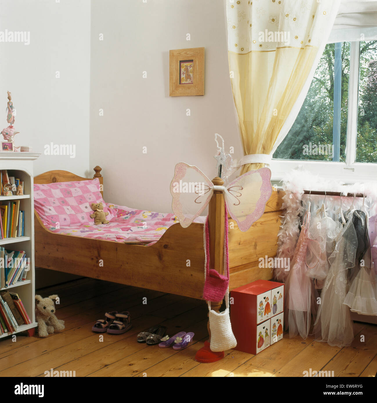 Pink bedlinen on child's pine bed in girl's bedroom with cream curtains on the window - Stock Image
