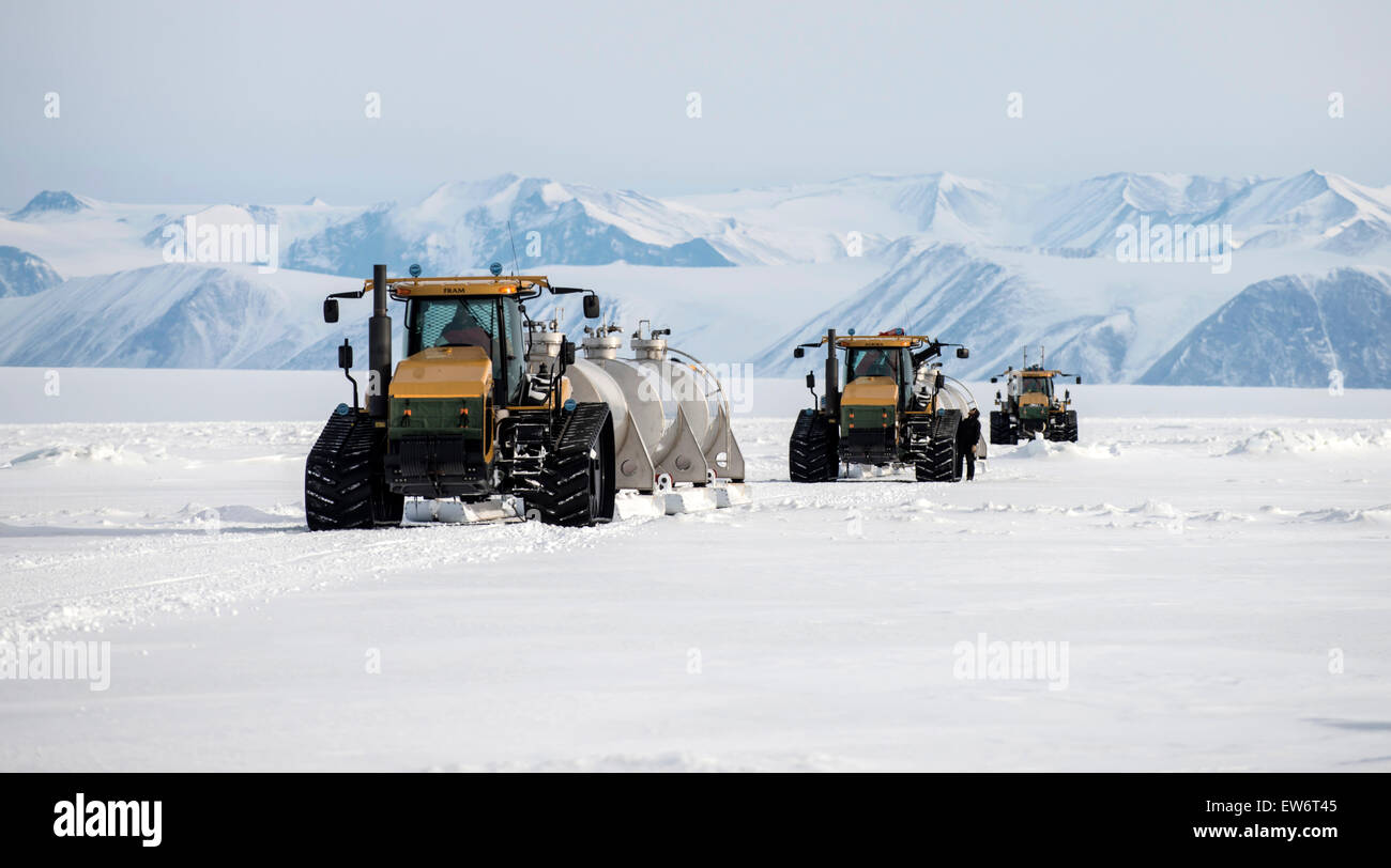 Tractors pull sleds of fuel to resupply a United States helicopter refueling station at Marble Point, Antarctica. - Stock Image