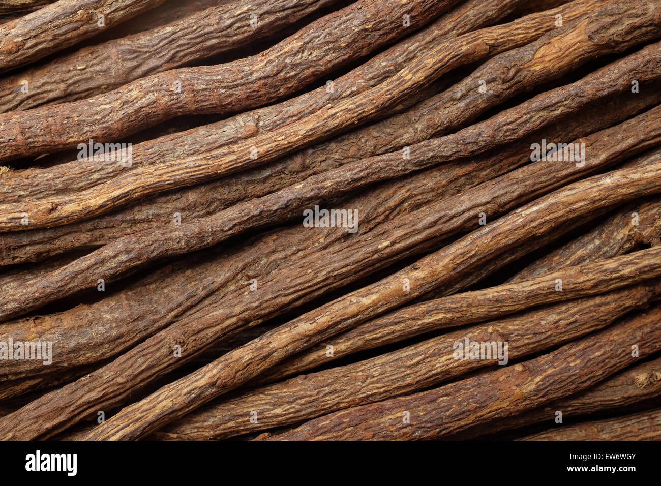 Pieces of liquorice root piled diagonally as an abstract background texture - Stock Image