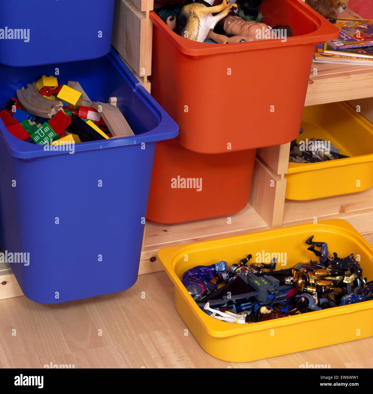 Close-up of brightly colored plastic bins storing children's toys - Stock Image