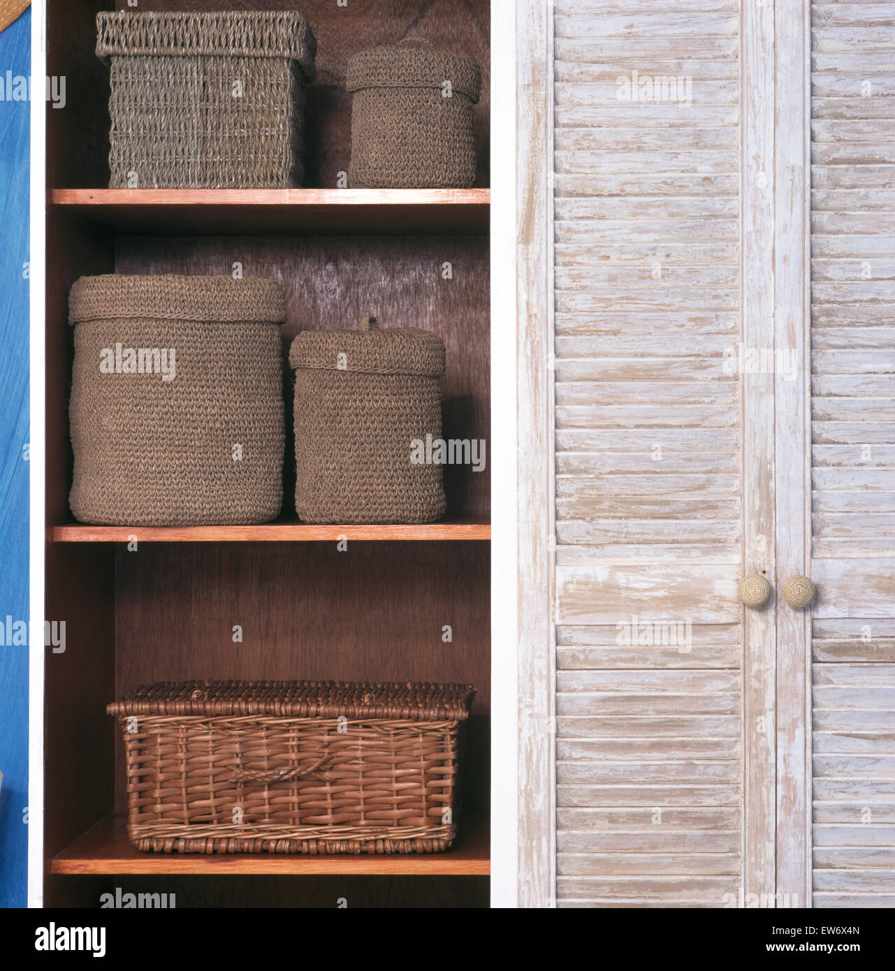 Close-up of cupboard with louvre doors and seagrass storage boxes and a wicker basket on shelves - Stock Image