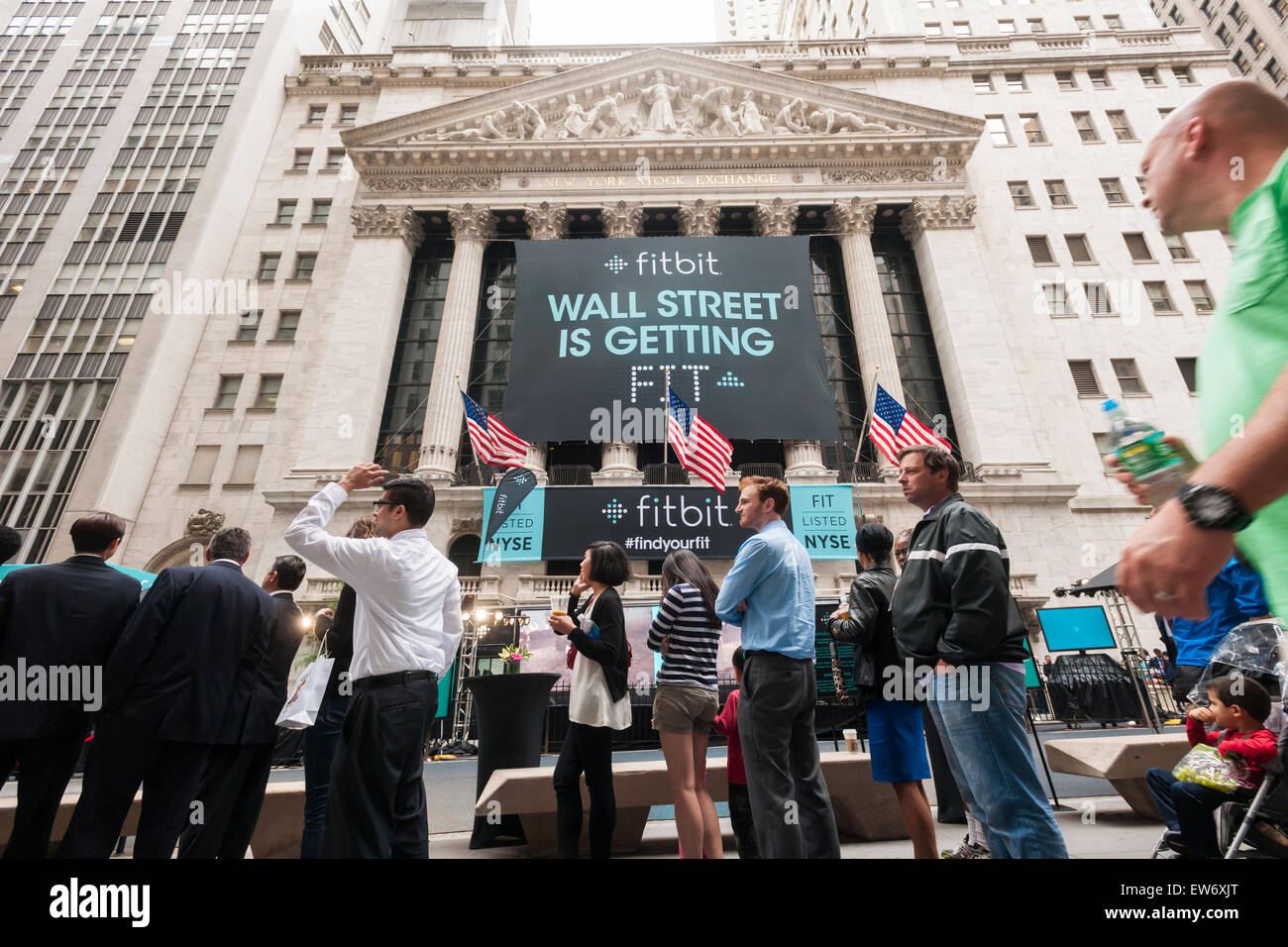 New York, USA. 18th June, 2015. People line up for free t-shirts outside the New York Stock Exchange decorated for - Stock Image