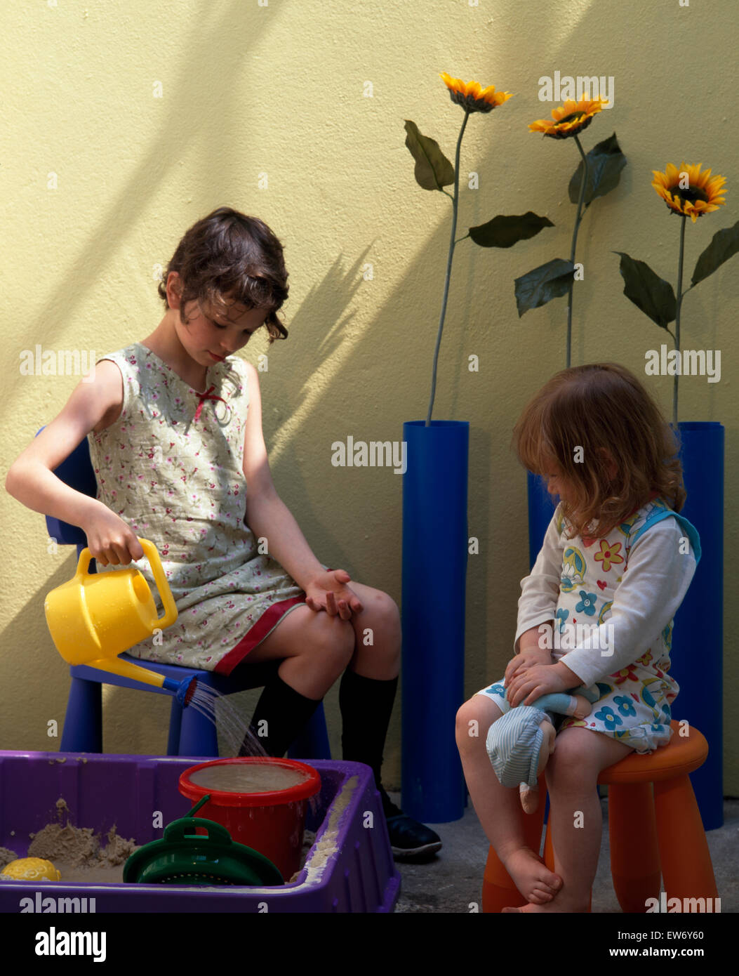 Two small girls sitting on chairs and playing with a watering can beside a sandbox - Stock Image
