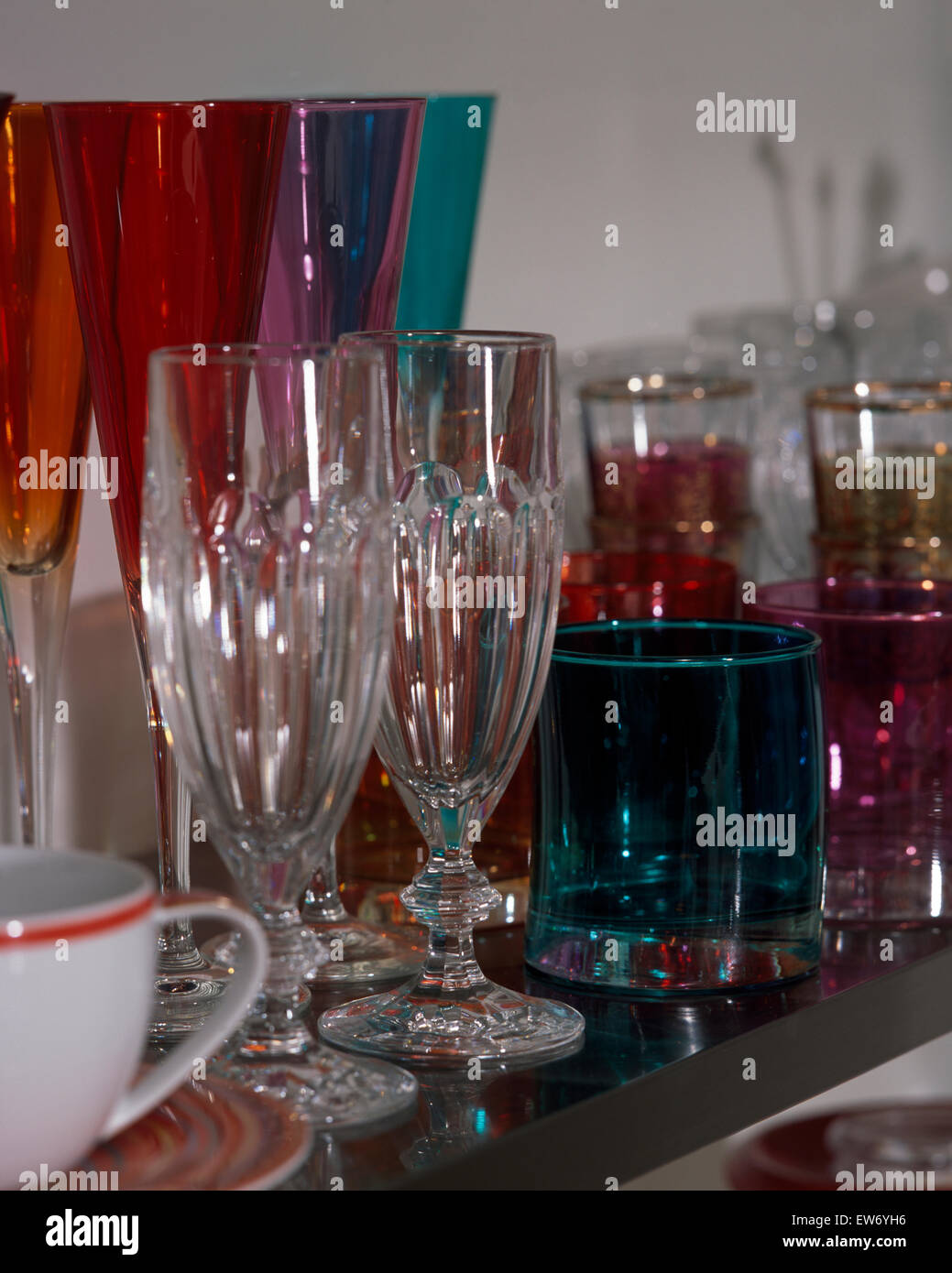 Close-up of a collection of clear and colored glassware - Stock Image