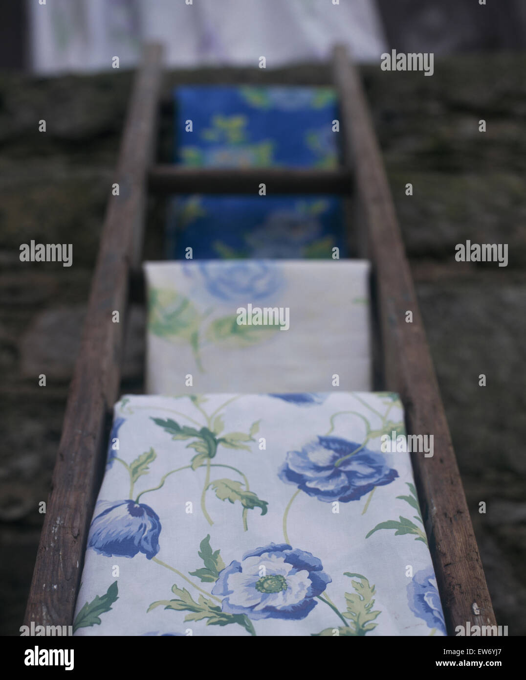 Close-up of blue poppy patterned bedlinen on a rustic wooden ladder - Stock Image