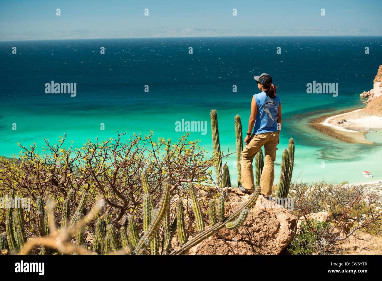 Mexico, Baja, Lapaz, Espiritu Santo. Woman standing on rock. - Stock Image