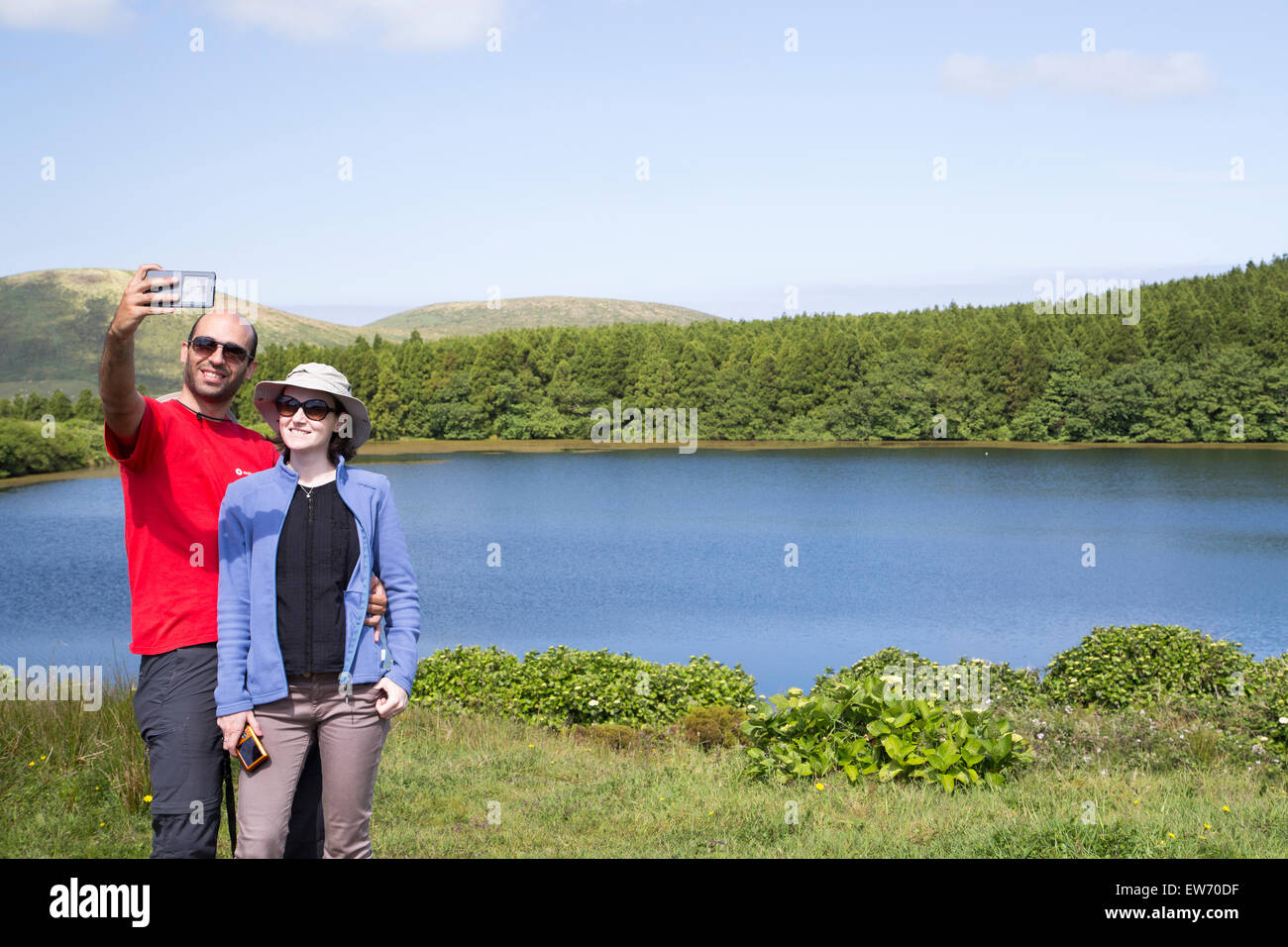 A couple of tourists taking a selfie image at one of the seven volcano lakes in Flores island. (This one is lake Stock Photo