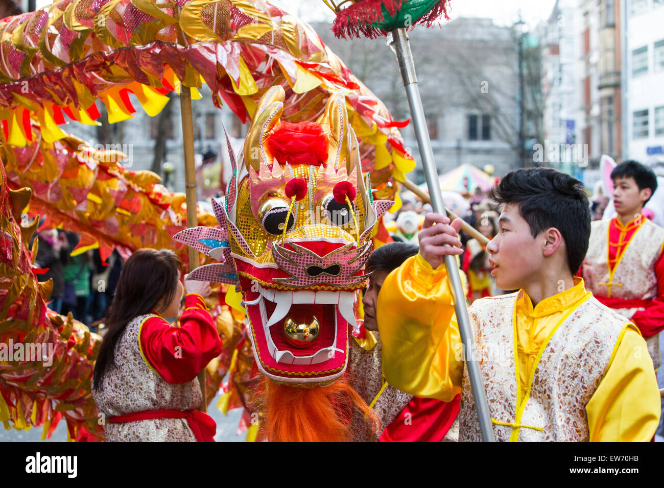 People in traditional Chinese costume with Chinese paper dragon, celebrating Chinese New Year in London - Stock Image
