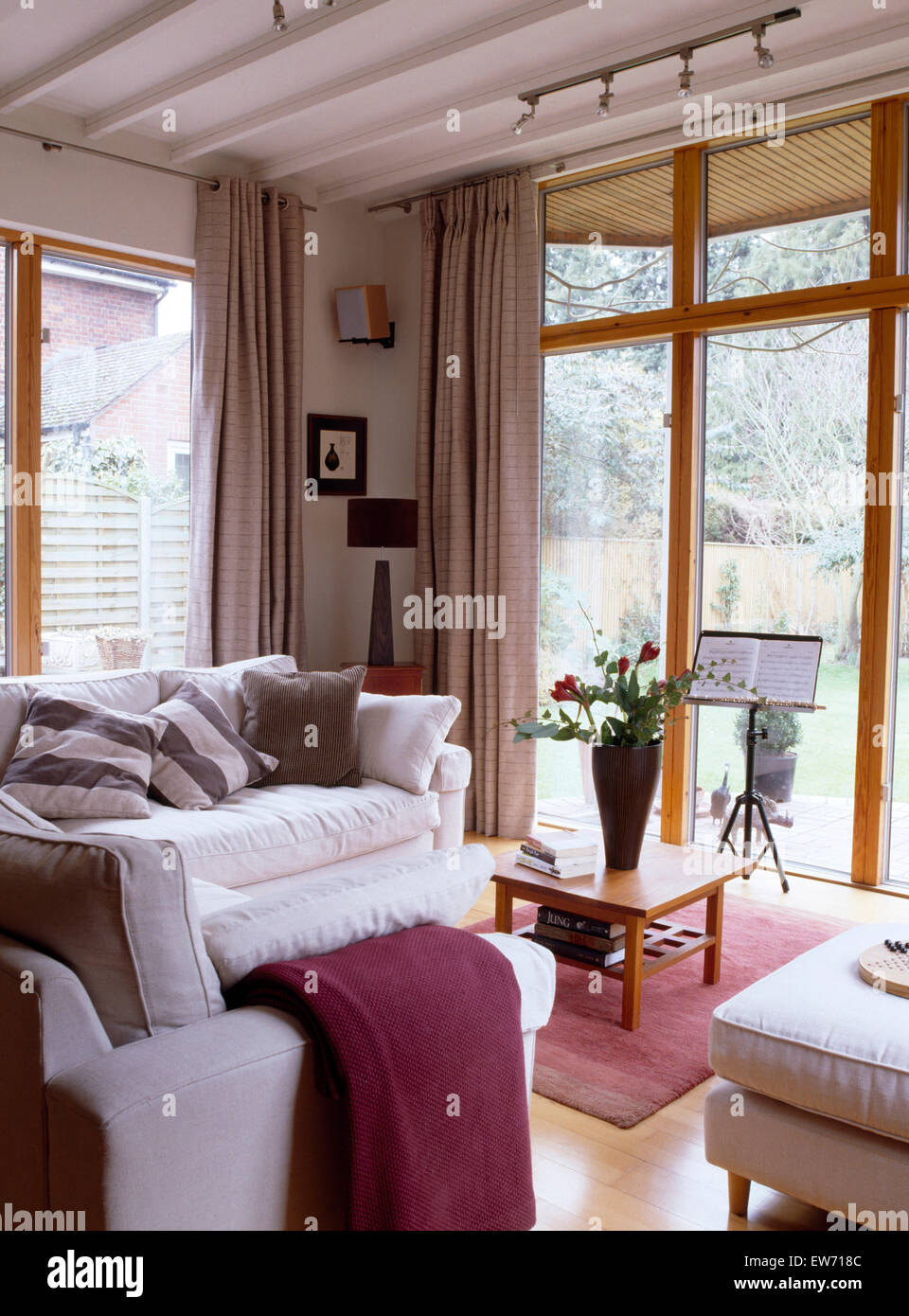 White sofas in modern living room extension with glass doors to the garden - Stock Image