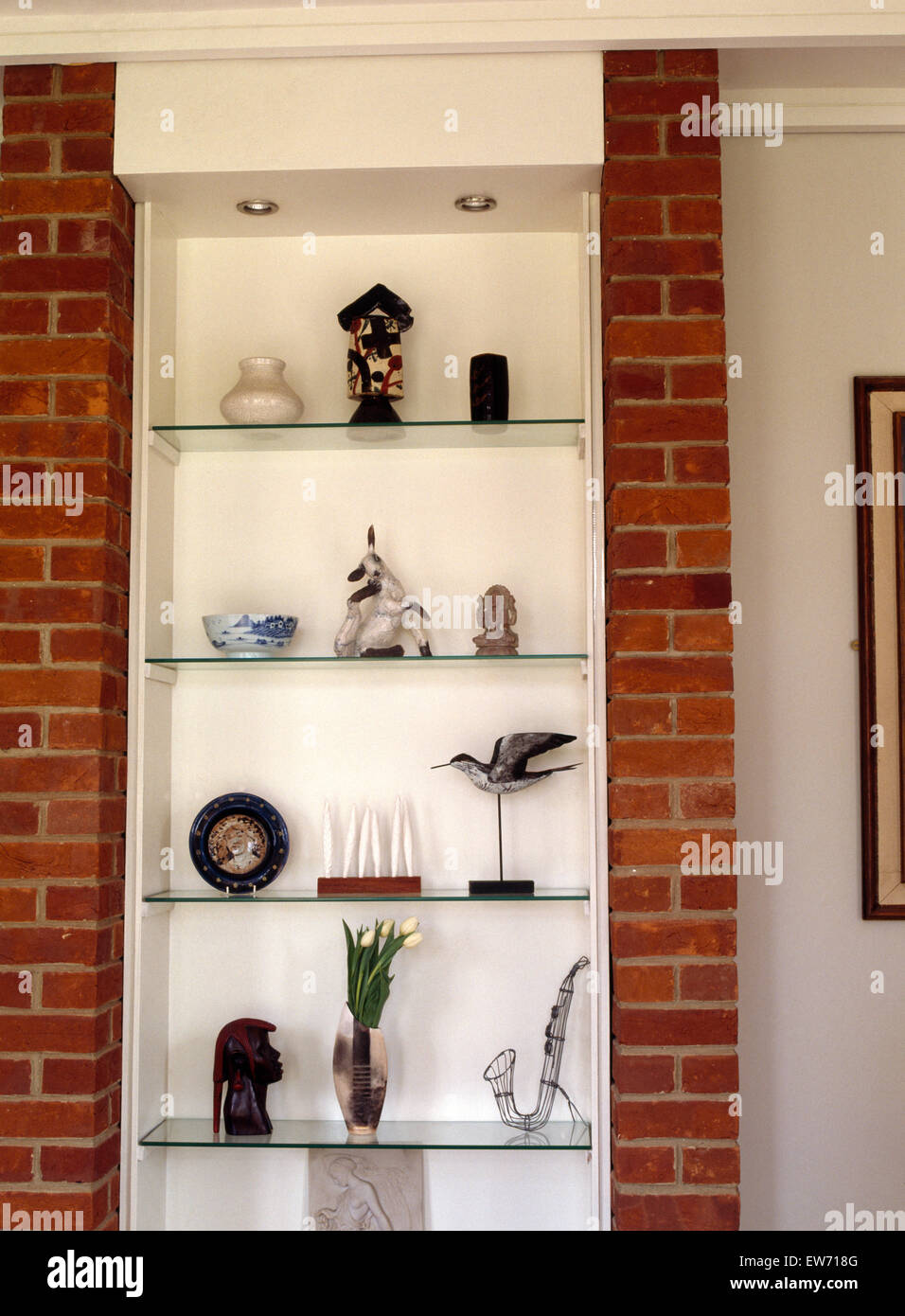 Close Up Of Ornaments On Glass Shelves With Brick Pillars In Modern Dining  Room