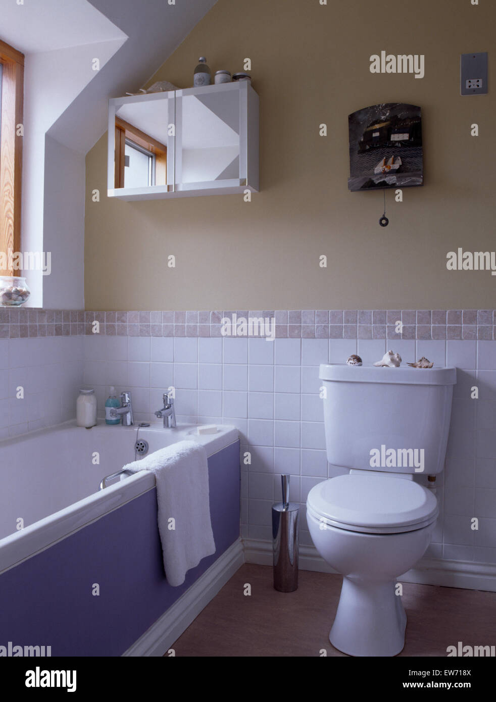 Toilet and bath with mauve panel in small bathroom with white tiles ...
