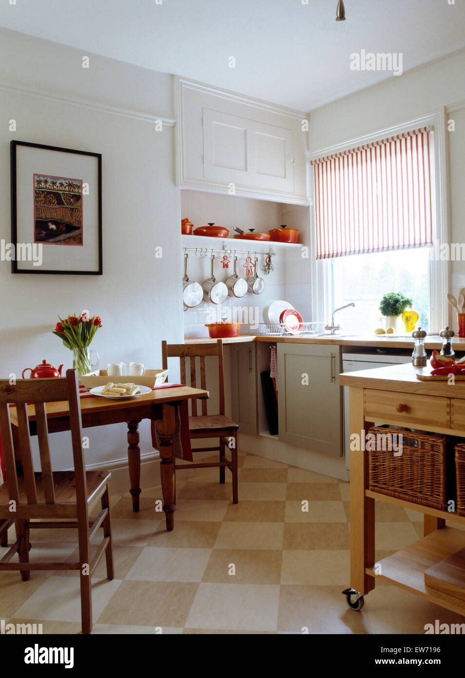 Cream checkerboard tiled flooring and striped blind in white country kitchen with wooden dining table and chairs - Stock Image