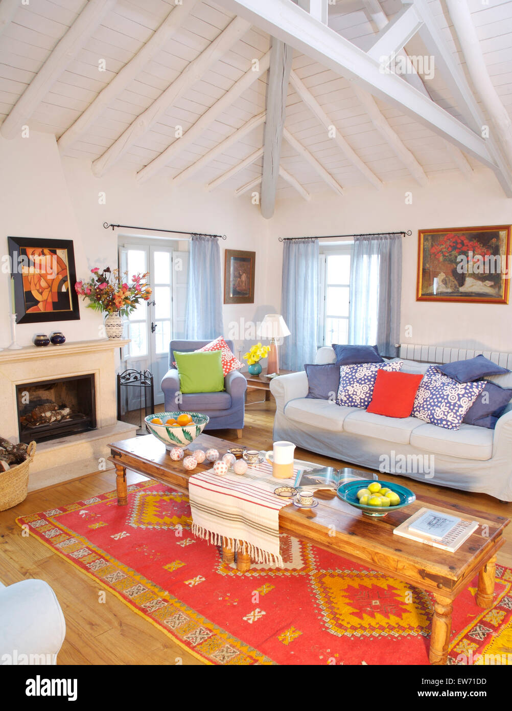Rustic Wooden Coffee Table On Red Ethnic Rug In Spanish Country Living Room  With White Painted Beamed Ceiling