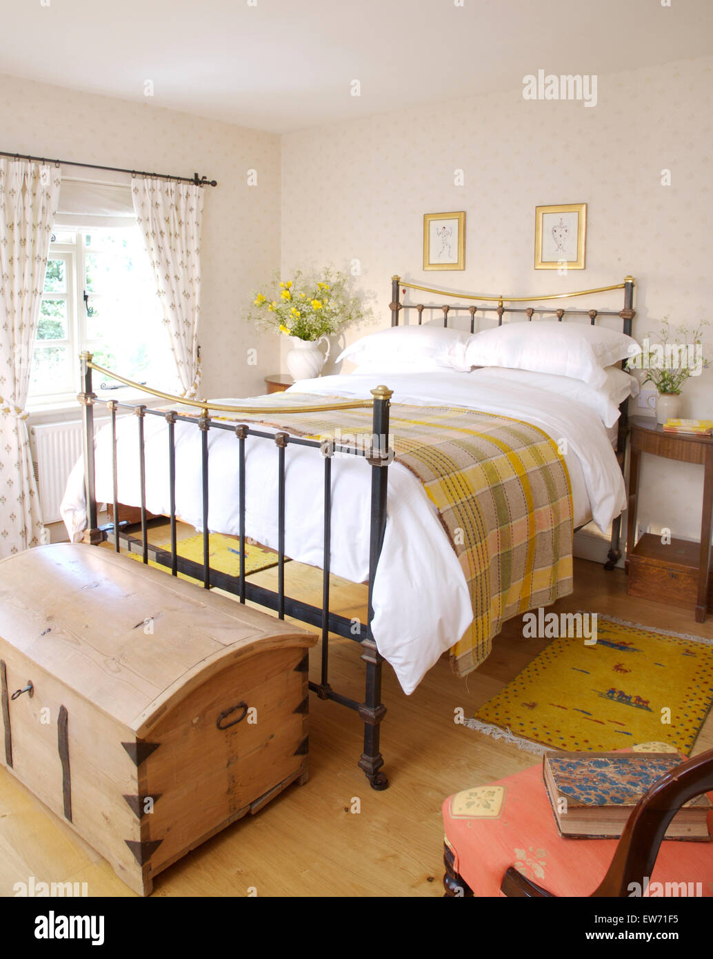 Pine Chest At The Foot Of A Brass Bed With White Bedlinen And A