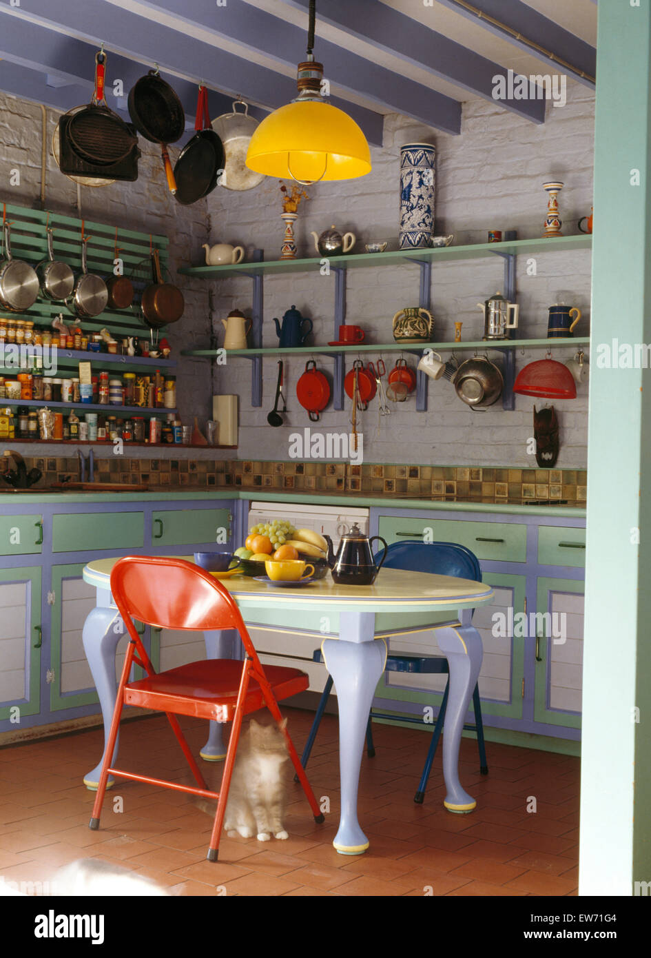 Painted fitted units and dining table with colorful plastic chairs ...