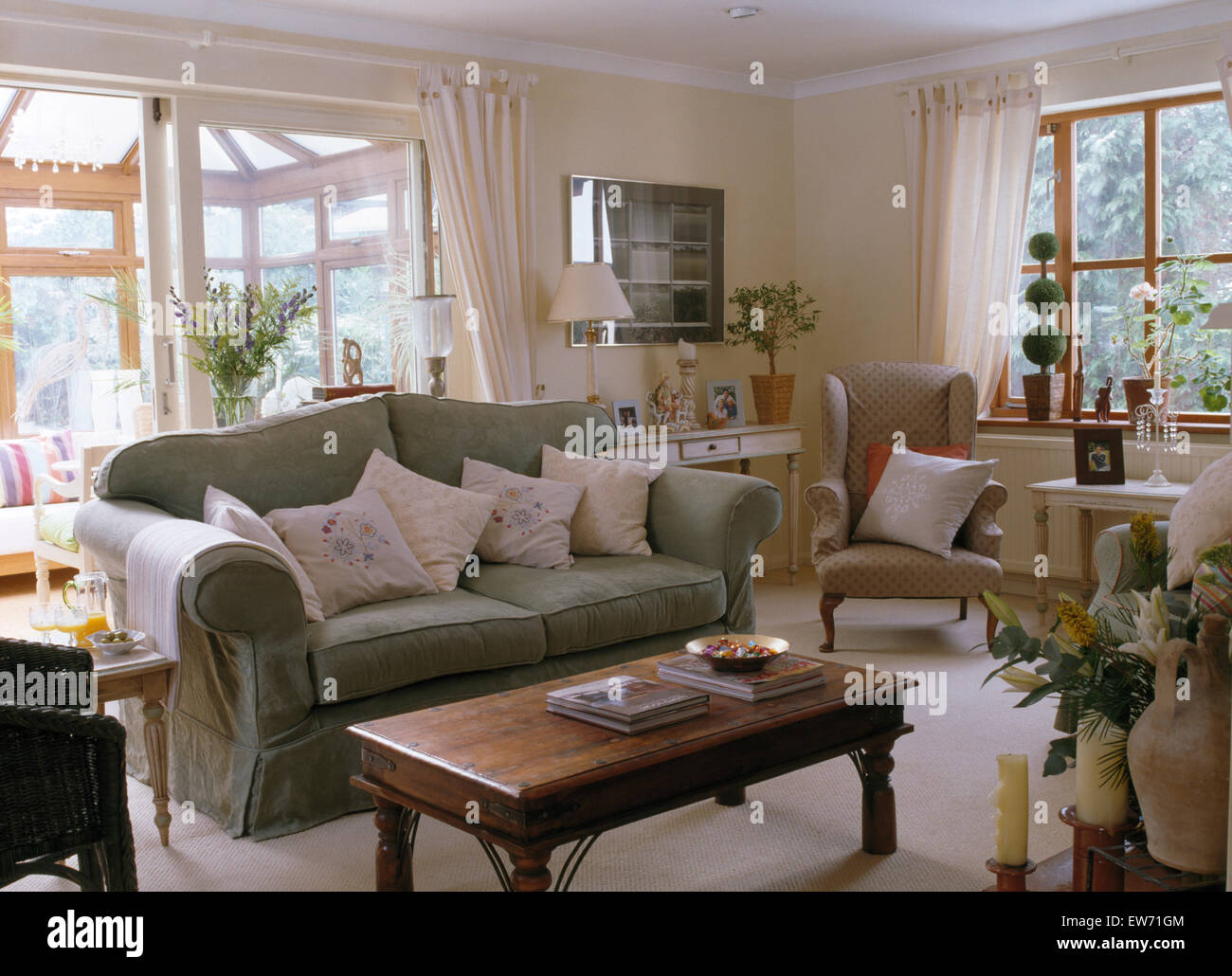 pale cushions on sage green sofa beside indonesian wood table in rh alamy com sage colored sofas sage green sofa covers