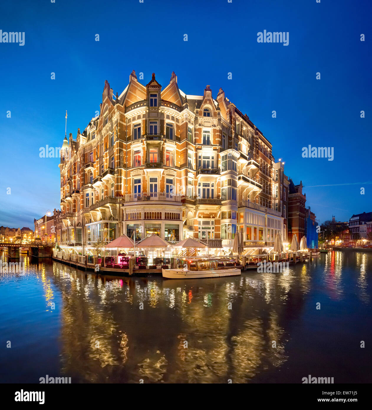 Amsterdam Hotel De l'Europe on corner of Amstel River and Rokin canal. Historic five star hotel in romantic - Stock Image