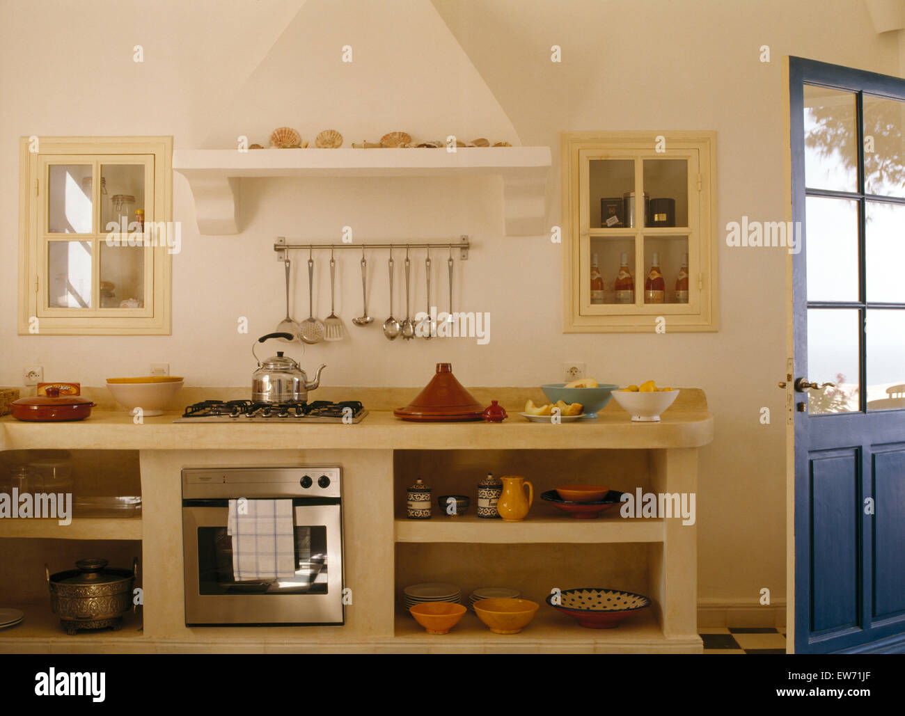 Glass Doors On Alcove Cupboards Above Polished Concrete Shelves With Stainless Steel Oven In Modern Moroccan Kitchen