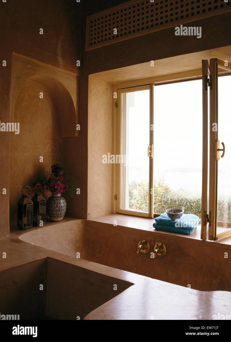 Moulded, polished concrete bath below window in modern Moroccan bathroom - Stock Image