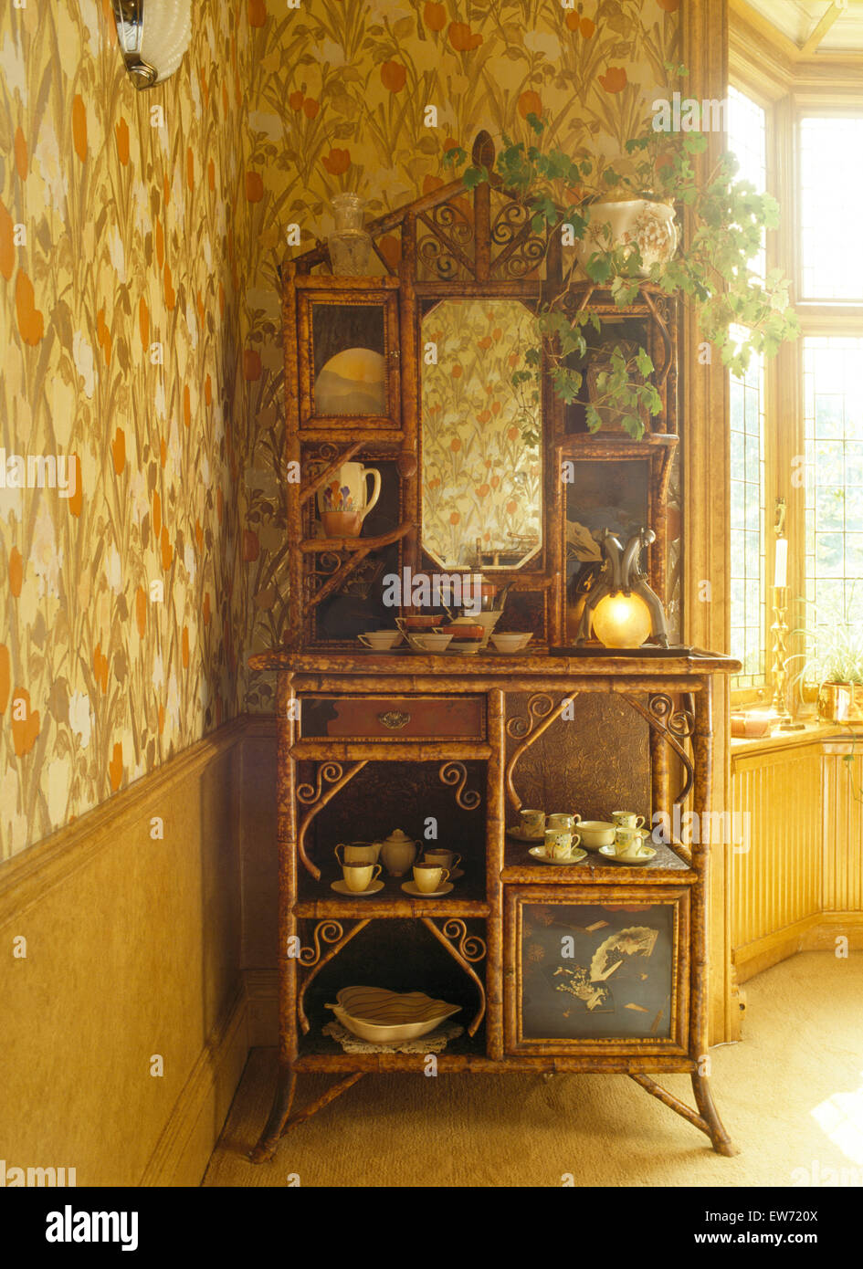 Edwardian bamboo cabinet in eighties hall with patterned wallpaper - Stock Image