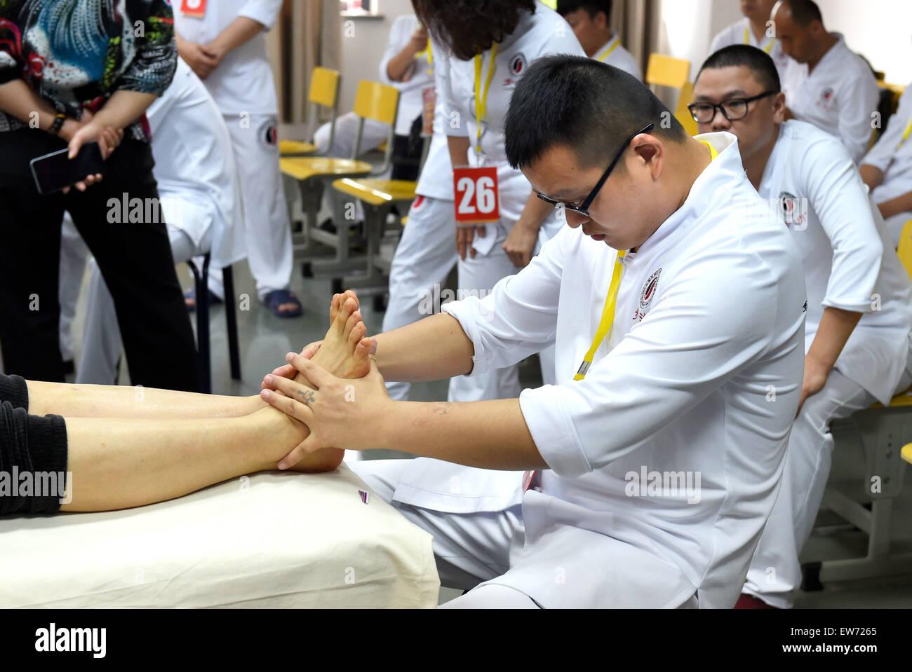 Nanjing, China's Jiangsu Province. 18th June, 2015. A foot masseur takes  part