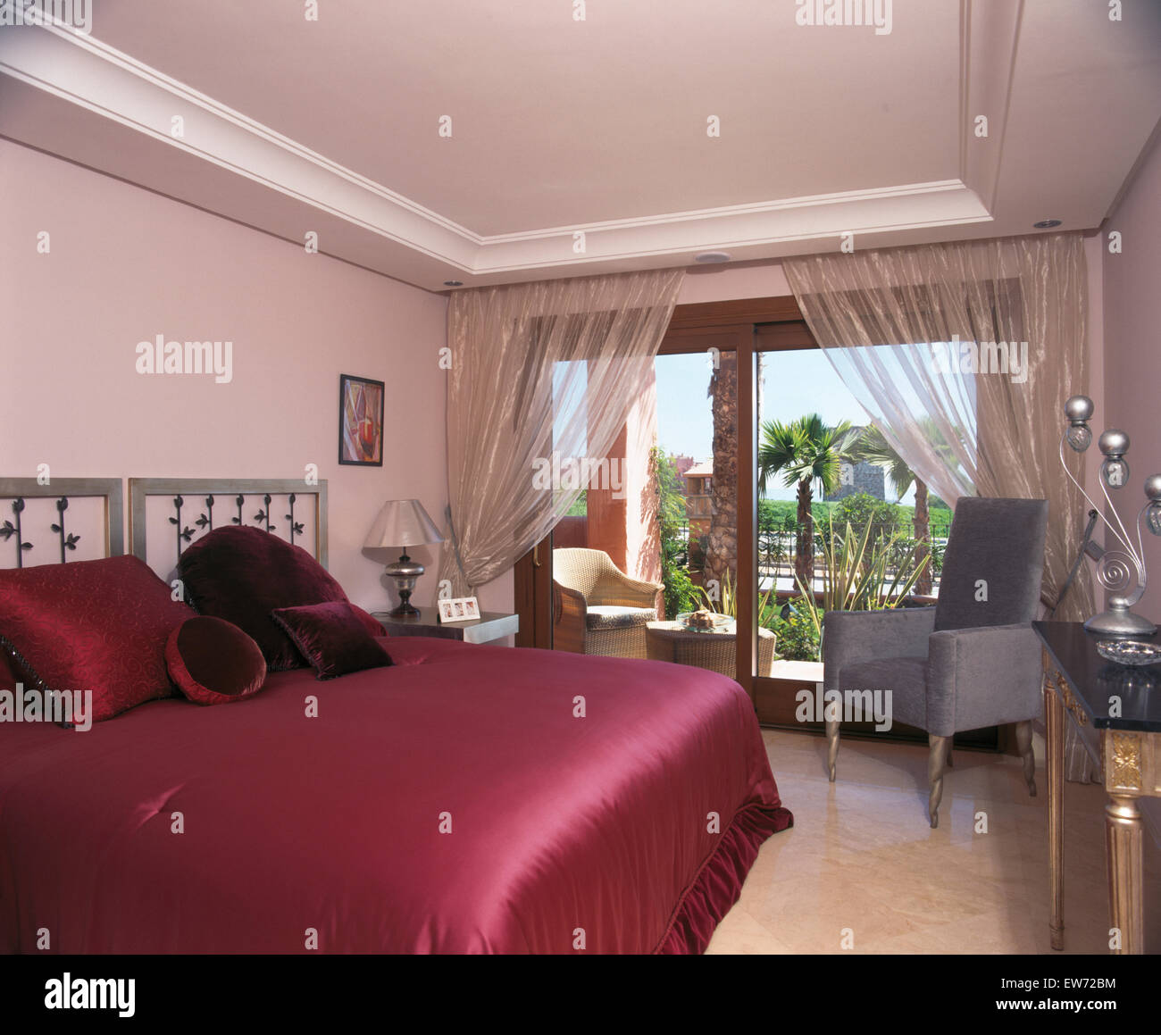 Dark Pink Satin Bed Cover On Bed In Spanish Apartment Bedroom With Sheer  Organza Drapes On Patio Doors