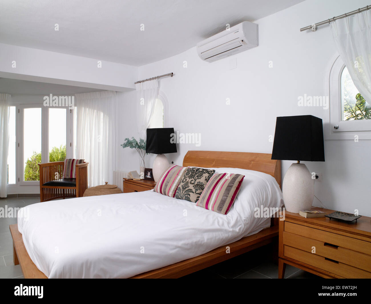 Small air-conditioning unit above bed with white duvet and striped ...