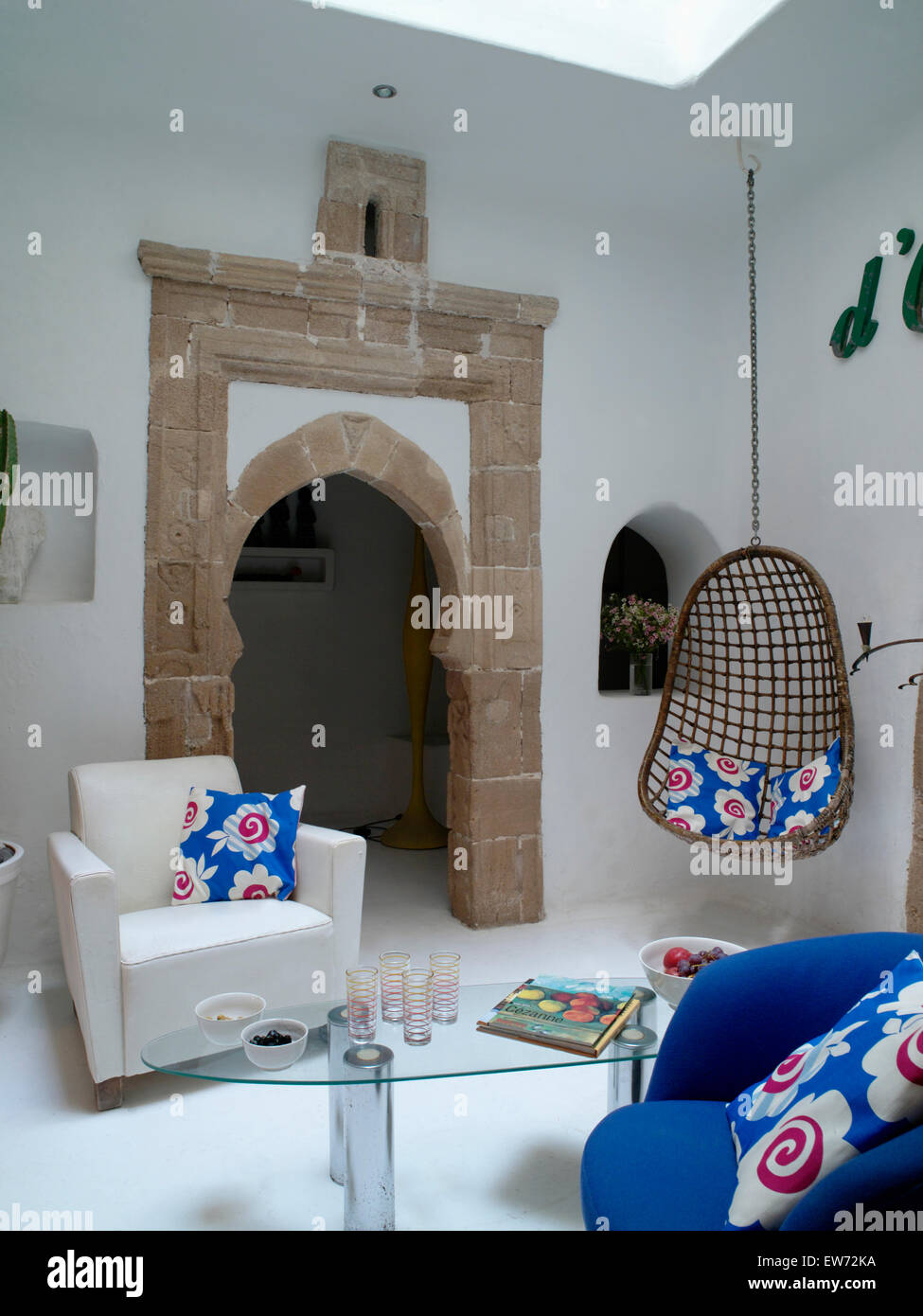 Modern Moroccan Living Room With White Armchair And Suspended Chair On  Either Side On Stone Doorway To Hall