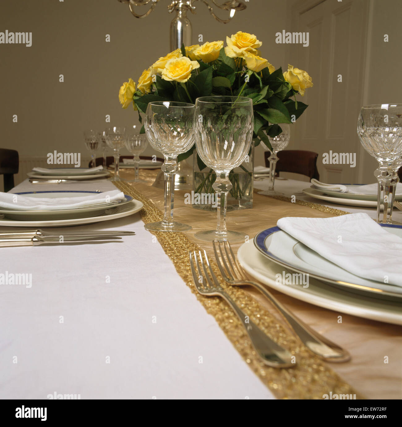 Close-up of a vase of yellow roses on table set for dinner with silver cutlery and white plates - Stock Image