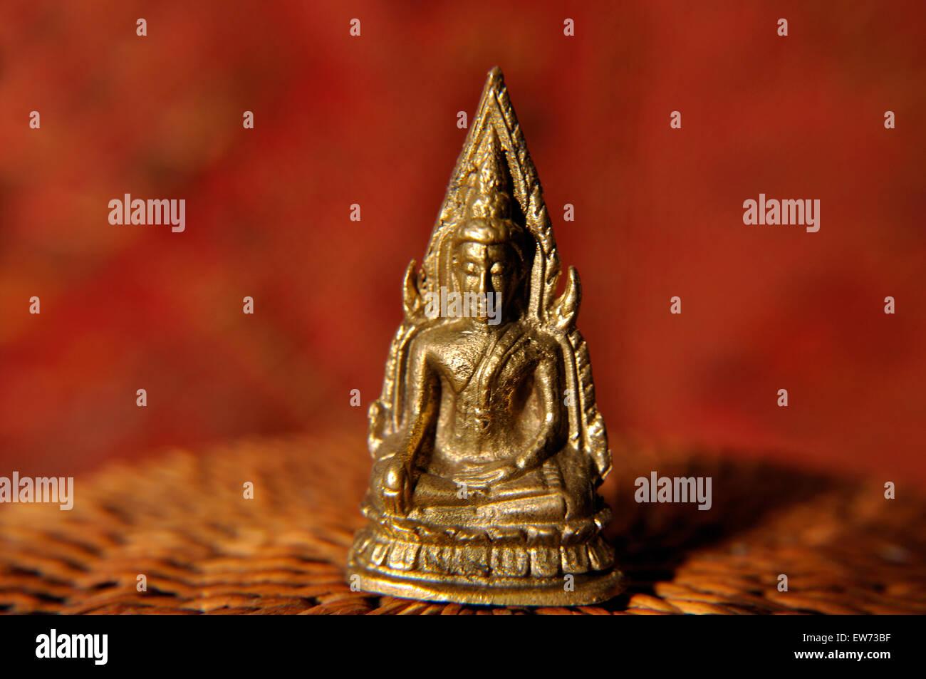 Miniature Thai Buddhist amulet in studio setting - Stock Image