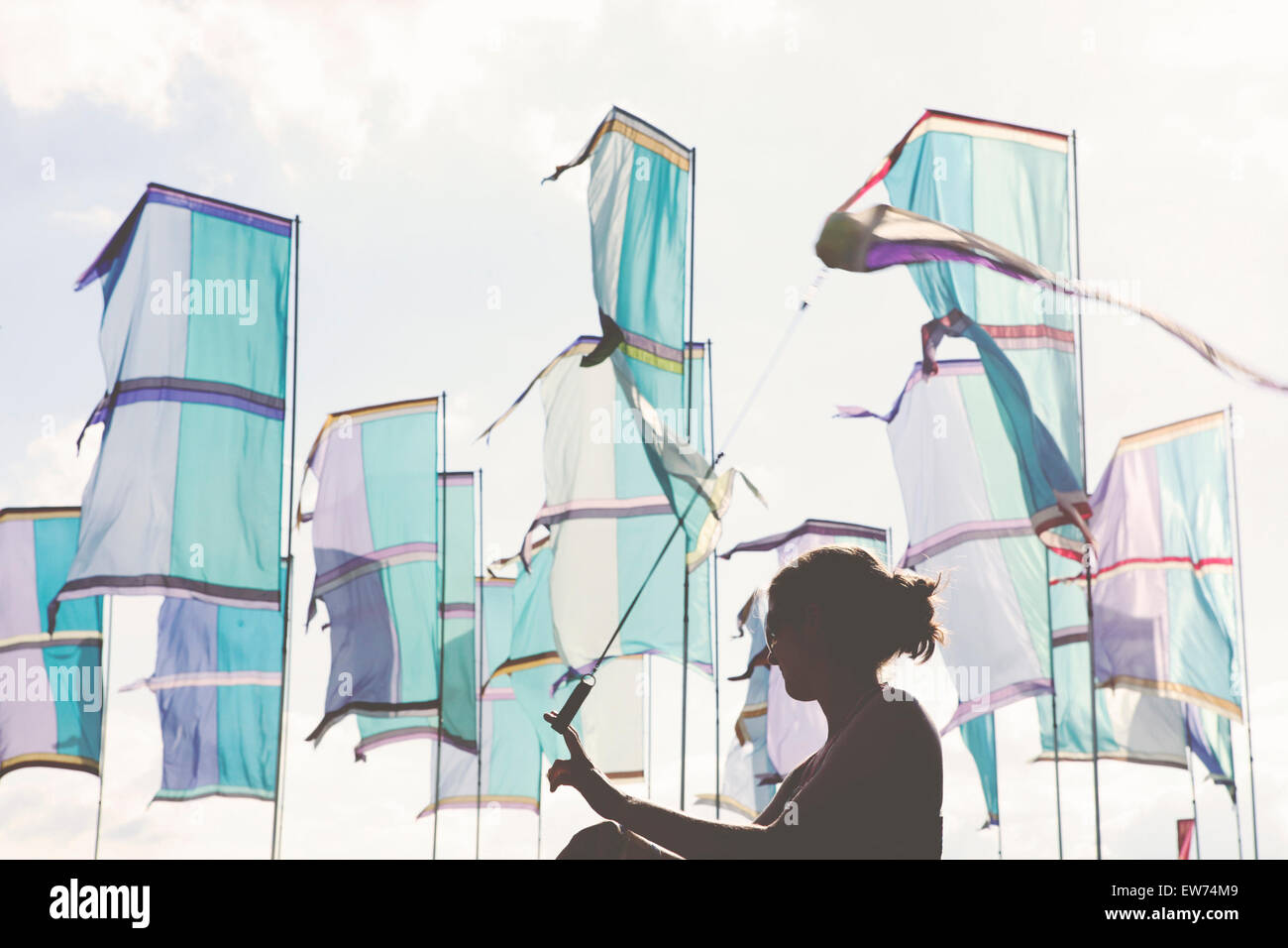 Flags and silhouette of girl dancing at summer music festival - Stock Image