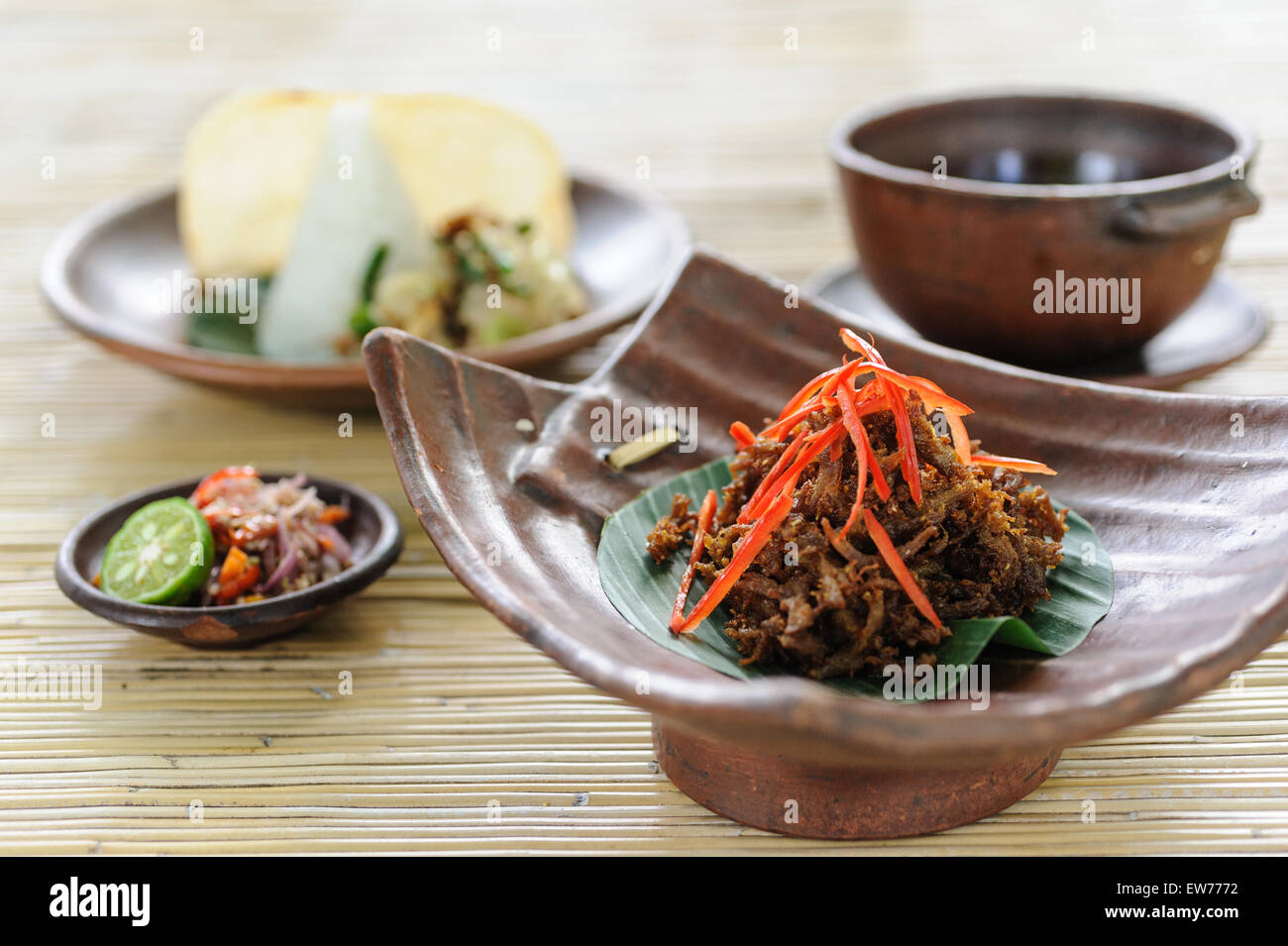 Balinese crispy duck garnished with chillies and served with sambal, soup, rice and vegetable. - Stock Image