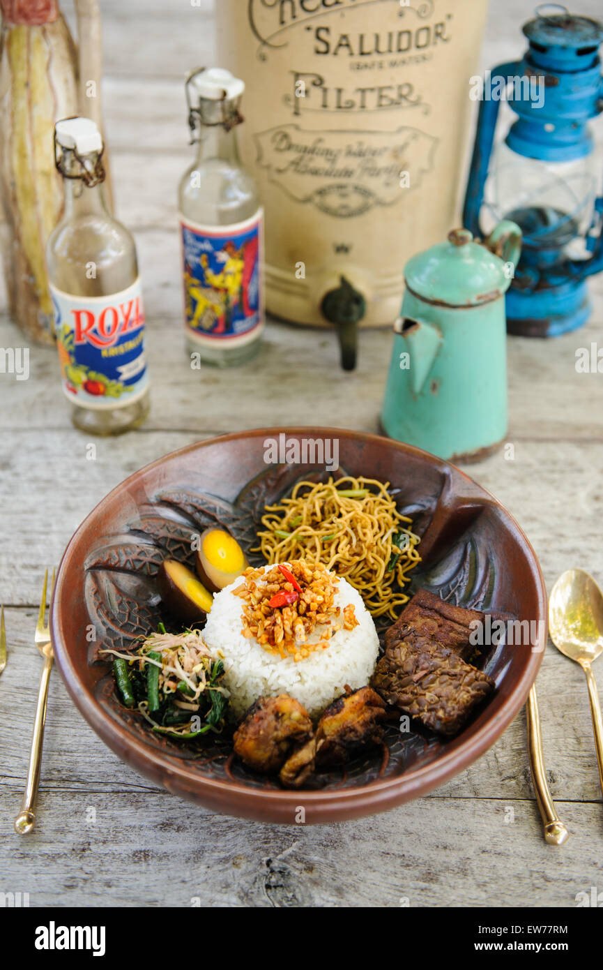 Indonesian nasi campur with fried chicken, noodles, eggs, tempeh and vegetables. - Stock Image