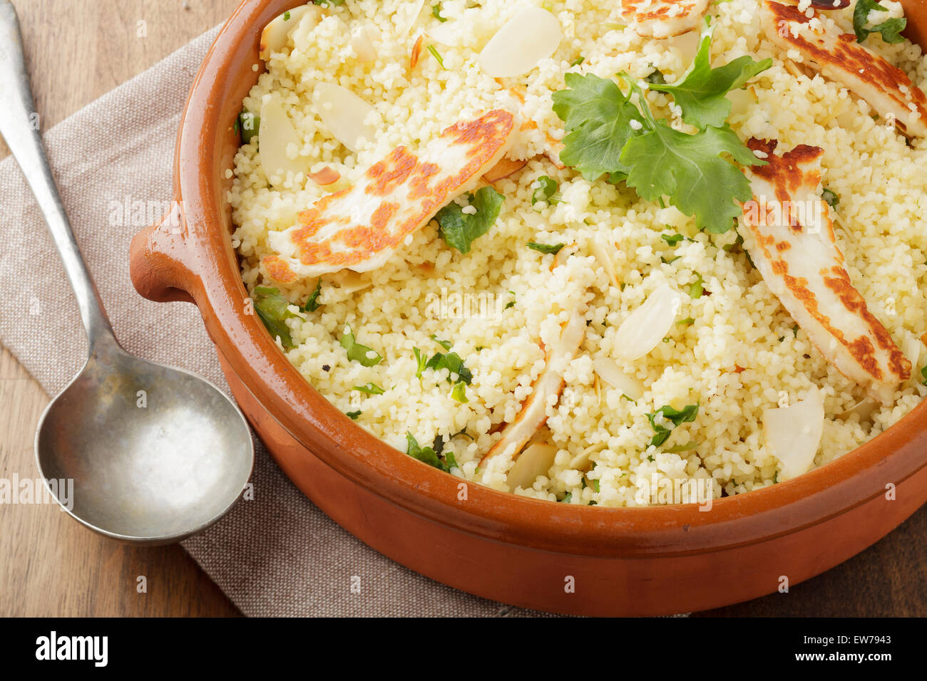 Lemon and parsley couscous with almonds and halloumi Stock Photo
