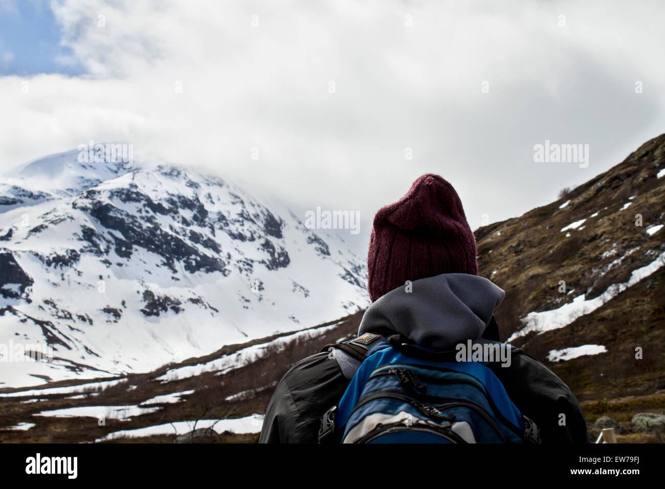 The mountains of Jotunheimen. A hiker is looking towards Galdhøpiggen - the highest peak in Norway. - Stock Image