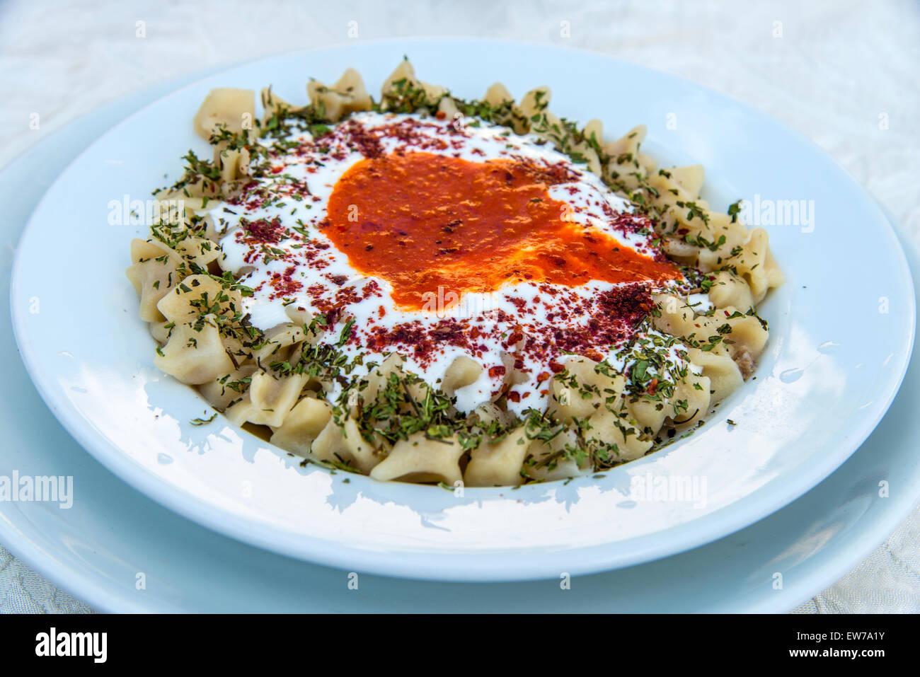 Traditional manti dumplings or Turkish ravioli served in a restaurant, Goreme, Cappadocia, Turkey - Stock Image