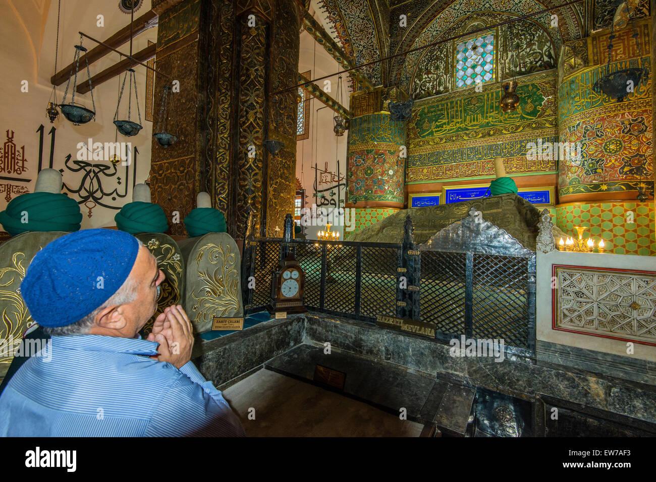 Worshiper praying on Mevlana's Tomb at Mevlana Museum, Konya, Turkey - Stock Image