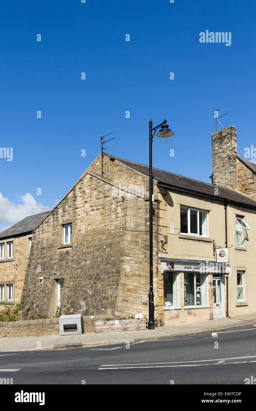 Unusual slanting buttress wall added to support the gable end of a house on the corner of The Bank/Bridgegate, Barnard - Stock Image